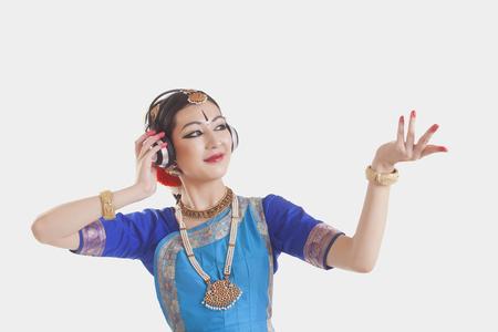 Bharatanatyam dancer wearing headphones while performing over white background Stock Photo
