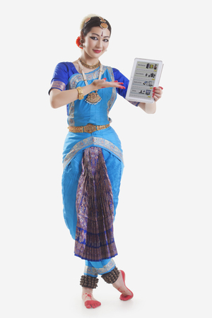 Full length portrait of Bharatanatyam dancer showing web page on digital tablet on while background Stock Photo