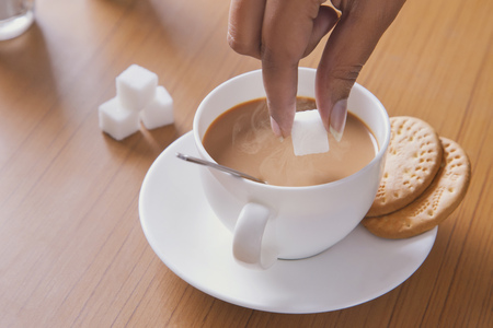 biscuits: Cropped image of woman adding sugar cube to tea
