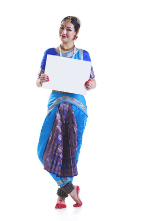 Full length portrait of Bharatanatyam dancer holding blank placard over white background