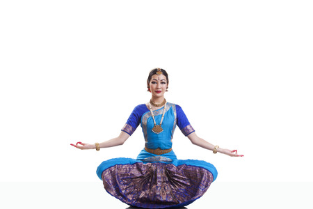 Full length portrait of dancer performing Bharatanatyam against white background
