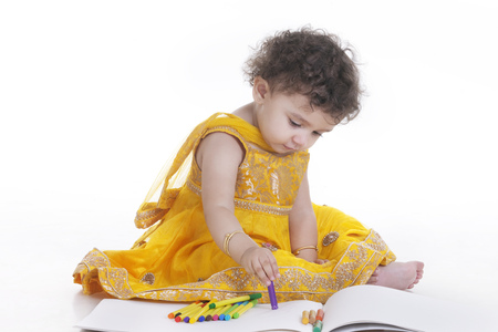 Full length of cute girl wearing salwar kameez drawing in book against white background