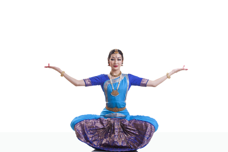 Portrait of dancer with arms outstretched performing Bharatanatyam against white background Stock Photo