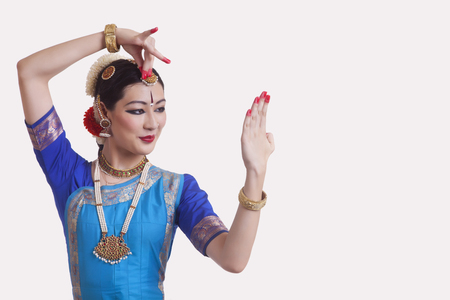Woman performing Bharatanatyam the classical dance of India on white background