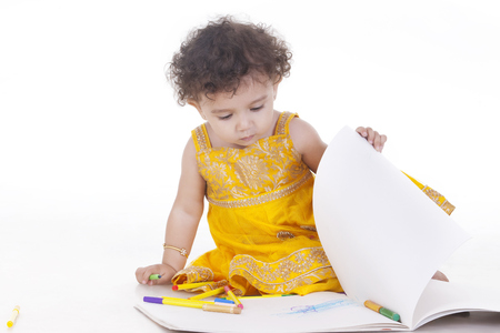 Cute girl turning page against white background