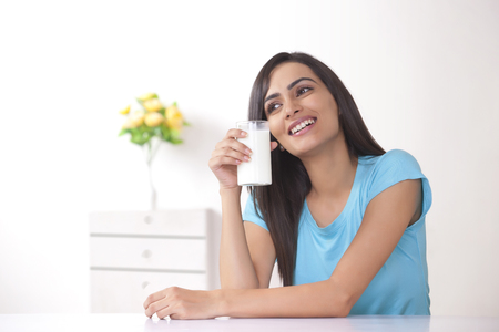 front house: Happy young woman holding glass of milk at home