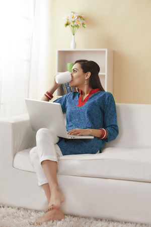 Young Indian woman with laptop drinking coffee on sofa Stock Photo