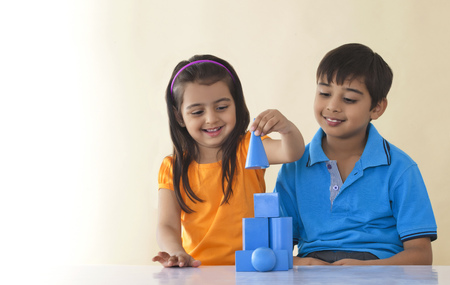 Smiling brother and sister stacking geometric shapes over colored background