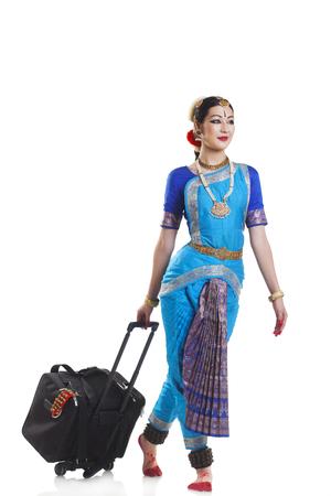 Full length of Bharatanatyam dancer with luggage walking over white background Stock Photo