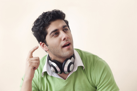 music background: Young man thinking while listening music Stock Photo