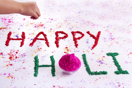 Hand writing HAPPY Holi with gulal over white background