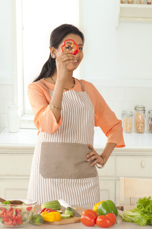 front house: Woman looking through bell pepper slice in kitchen Stock Photo