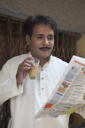 front view: Man drinking tea and reading a newspaper