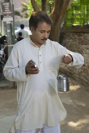 kurta: Man looking into a milk canister Stock Photo