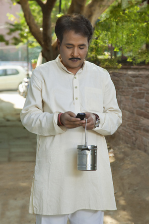 kurta: Man holding milk canister and using cell phone