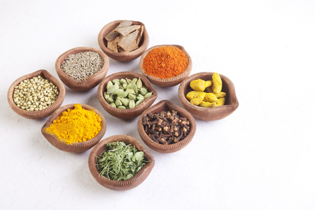 Variety of Indian spices in diyas on white background Stock Photo