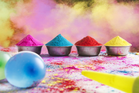 Containers of colorful Holi power arranged on floor with squirt gun and water bombs in foreground Stock Photo