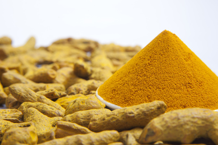 Turmeric powder and tumeric roots isolated on white background Stock Photo