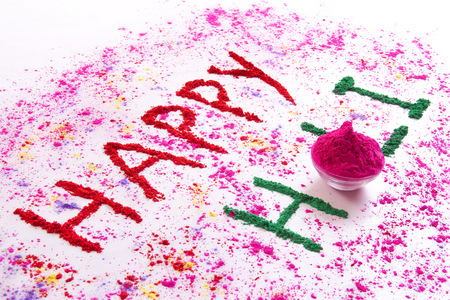 HAPPY Holi written with gulal over white background