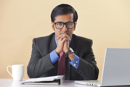 front view: Businessman sitting at computer desk