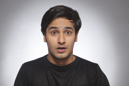 front view: Portrait of a young man looking surprised Stock Photo