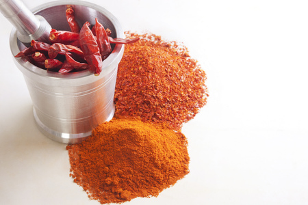 Crushed red chili peppers with chilies in mortar and pestle over white background