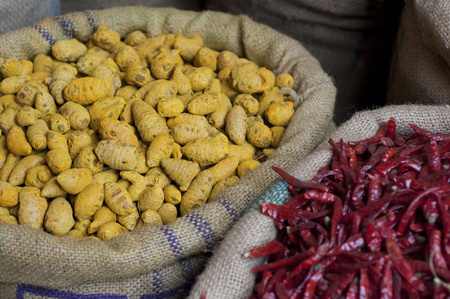 Sacks of dried chillies and turmeric root for sale at the market Stock Photo