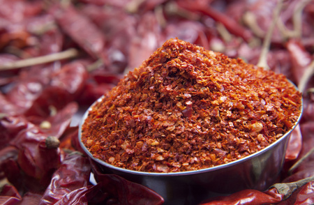 Close up of chilli powder in bowl and red chillies Stock Photo