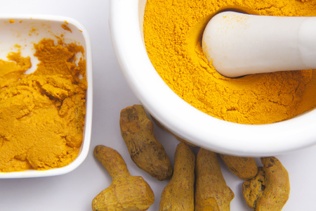Turmeric powder in a mortar with Turmeric roots and paste isolated on white background Stock Photo