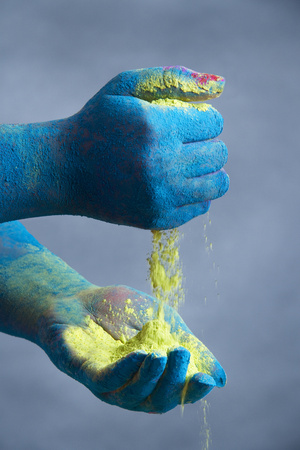Close-up of blue colored hands holding yellow powder paint Stock Photo