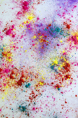 Multi-colored powder paint spread over white background