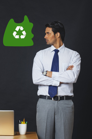front view: Digitally generated image of businessman looking at recycling symbol in office