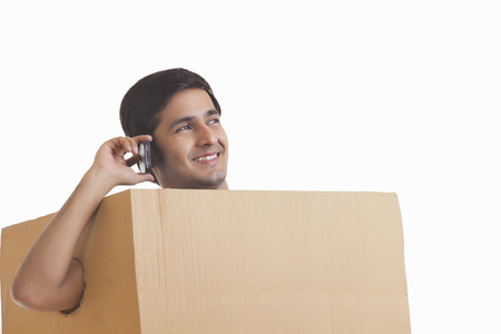 cardboard only: A smiling man in a box listening to music on headphones Stock Photo