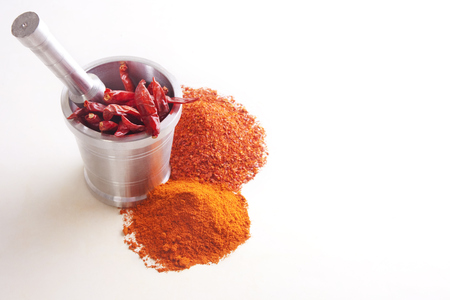 Chili powder with chili peppers in mortar over white background