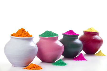 Row of pots filled with colorful Holi powder over white background