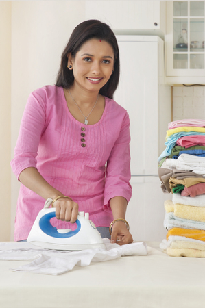 front view: Woman ironing clothes Stock Photo