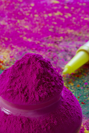 Close-up of pink Holi color powder with water gun in background
