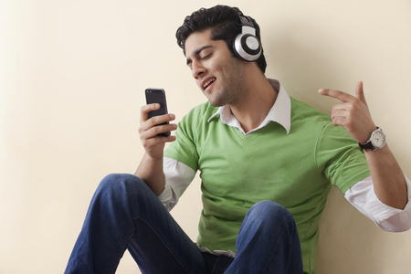 music background: Young man holding phone and listening to music Stock Photo
