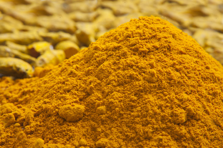 Heap of turmeric powder with tumeric roots on background Stock Photo