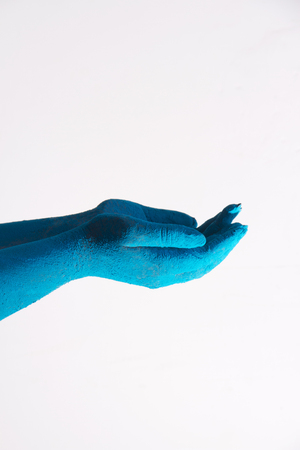 Close-up of blue colored cupped hands during Holi festival over white background Stock Photo