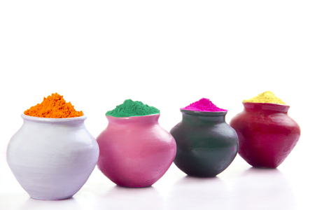 four objects: Row of pots filled with colorful Holi powder over white background