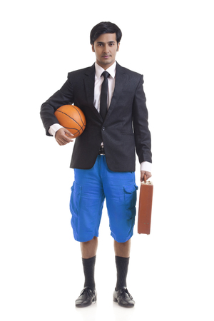 front view: Portrait of young man holding briefcase and basketball