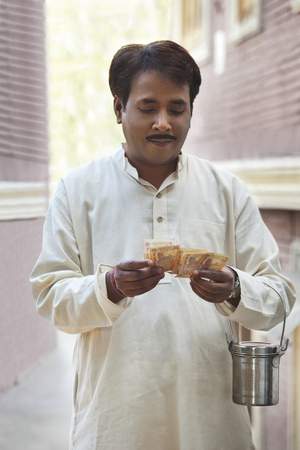 steel. milk: Man holding milk canister and counting rupees Stock Photo