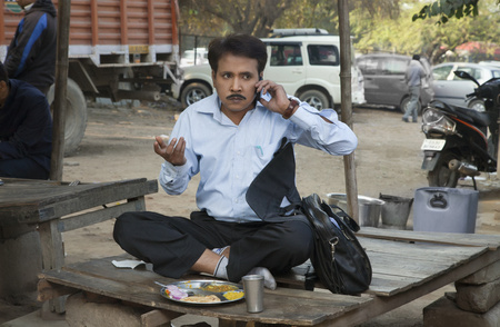 front view: Salesman having lunch and using cell phone