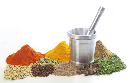 Mortar and pestle with variety of spices over white background Stock Photo