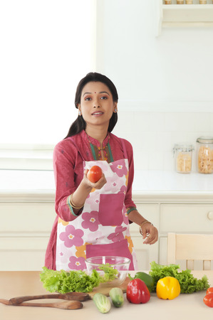 front house: Woman holding tomato in kitchen