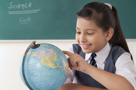 preadolescent: Close-up of girl looking at globe of world in a classroom
