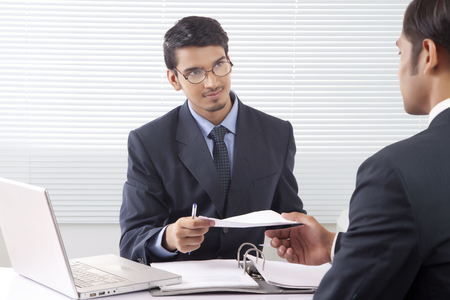 advice: Young professional man giving document to another professional man inside office cabin
