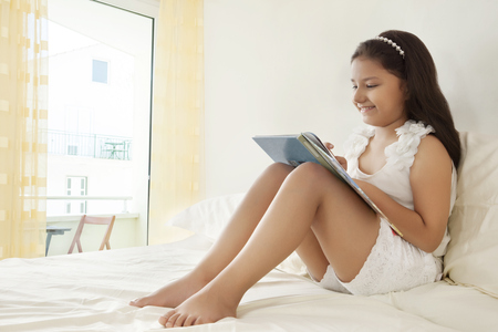 sit down: Girl reading book on bed
