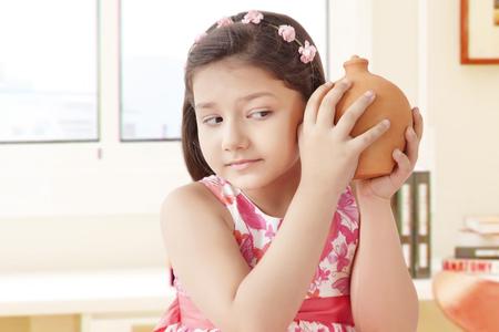 preadolescent: Girl holding clay piggy bank Stock Photo